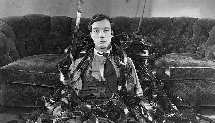 Buster Keaton surrounded by film in a still from the classic comedy Sherlock Jr.