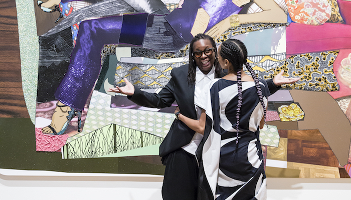 Artist Mickalene Thomas and her partner Racquel Chevremont standing in front of Mickalene's portrait of Racquel at the Wexner Center for the Arts, September 13, 2018. Photo: Katie Spengler