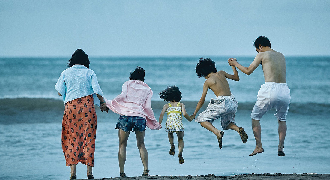 A family of five jumps into the shallow waves of the ocean