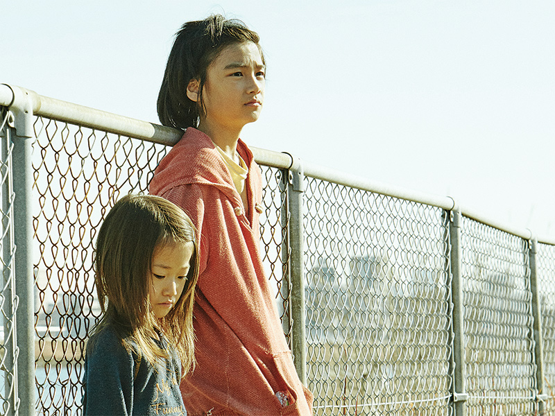 Two young girls stand along a fence