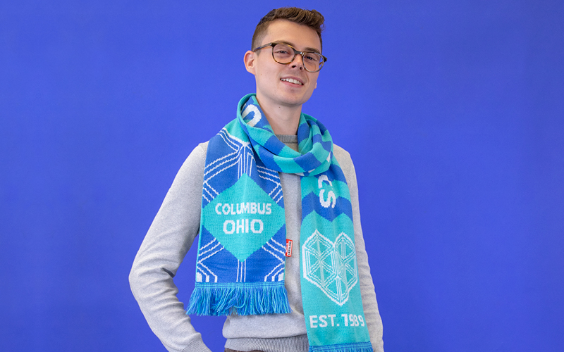 Wexner Center Design intern Michael Fletcher wearing the WEX Museum League Scarf by Maurizio Cattelan, designed exclusively for the Wexner Center Store