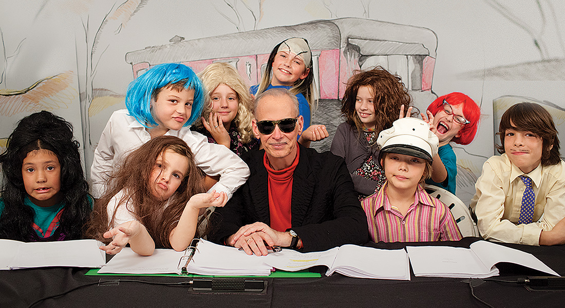 John Waters surrounded by a large group of children