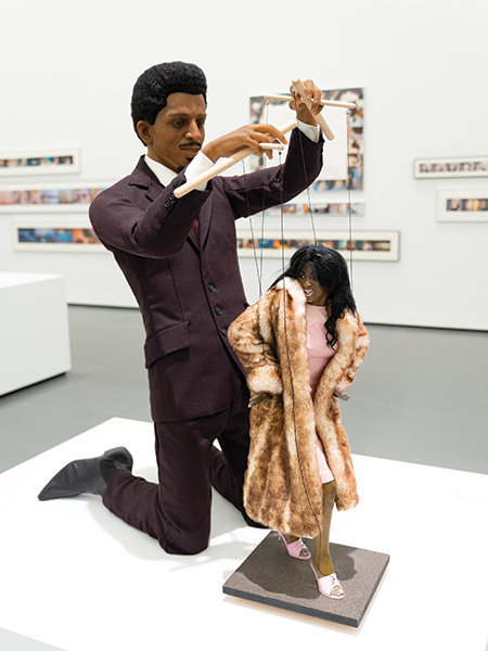 Sculpture of a man pulling puppet strings on a female figure