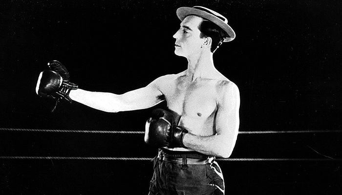 Man in hat poses with boxing gloves in a fighting stance