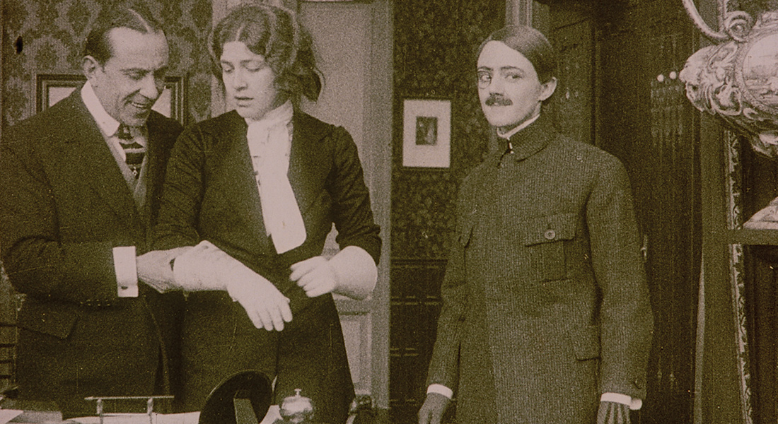 A woman disguised in men's clothing stands next to an older man and woman
