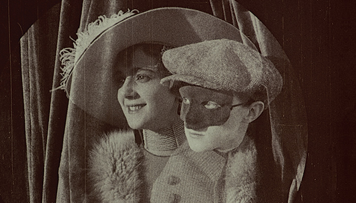 A person in disguise peaks over the shoulder of a woman in a big hat