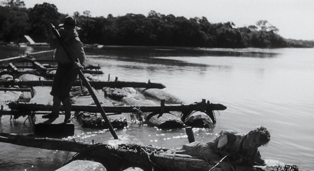 Fishers stand on logs in the water