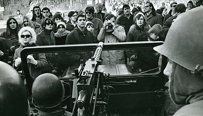 A crowd of protestors stand in front of a jeep carrying soldiers