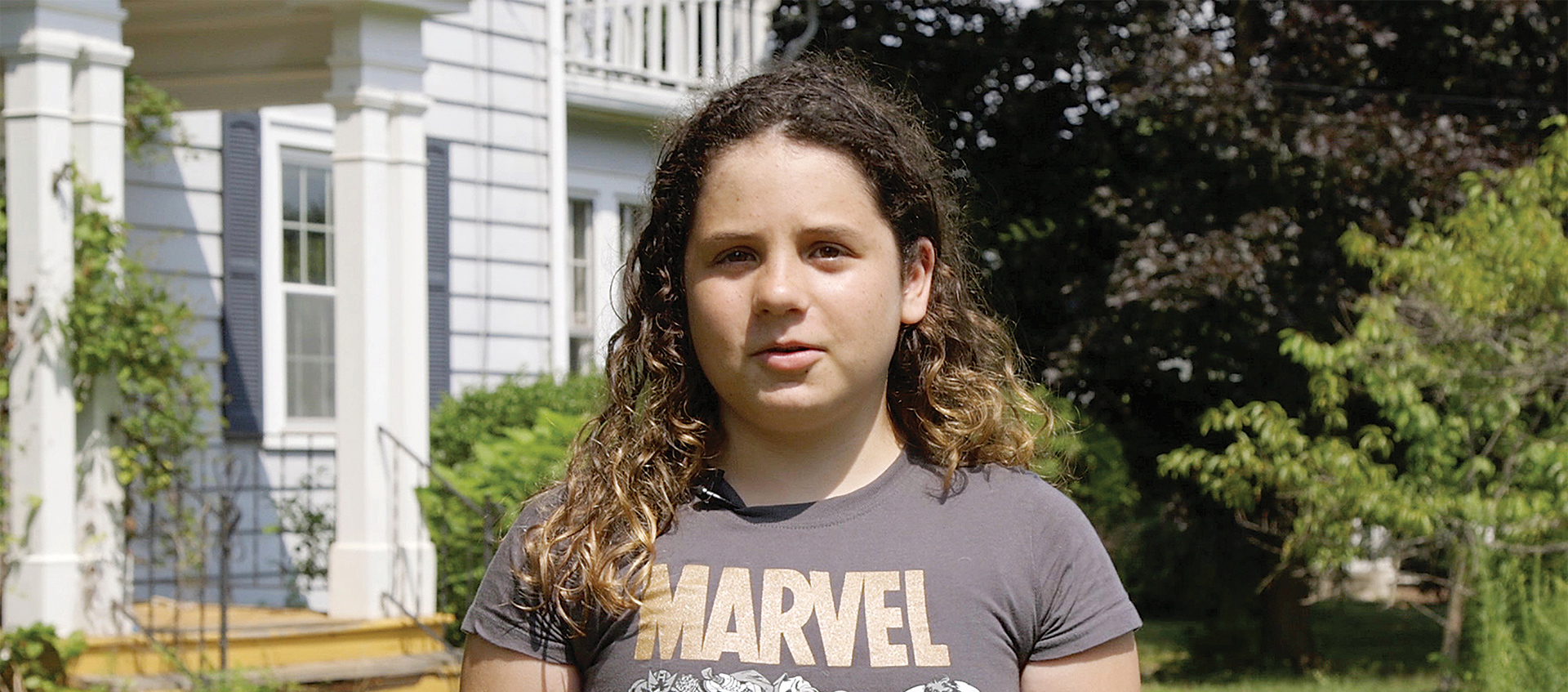 A girl in a Marvel T-shirt stands in front of a home