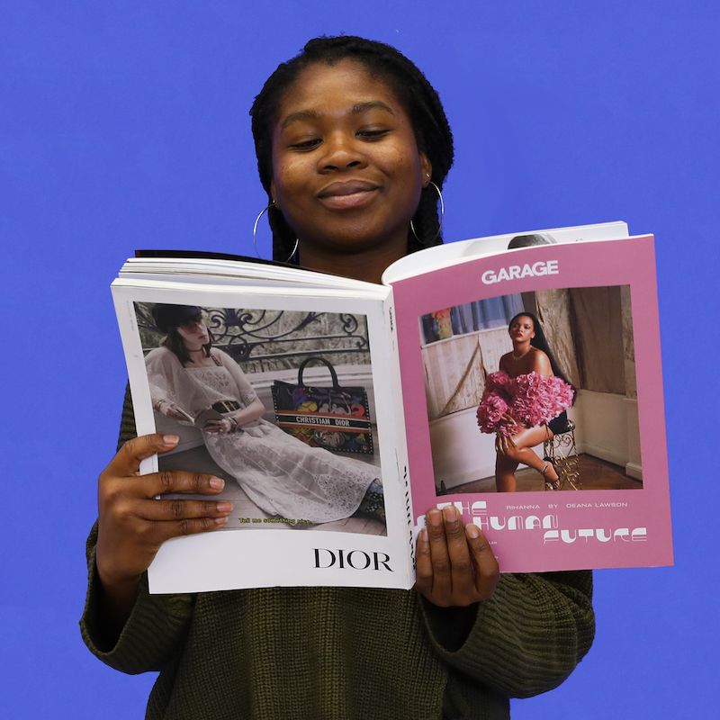 Wexner Center for the Arts Customer Service Student Assistant Seyi Adeyemi with a copy of the magazine Garage for the 2018 holiday gift guide