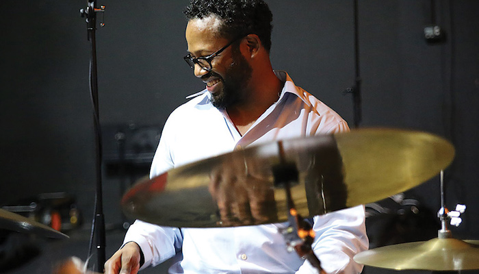Jazz musician, composer, educator, and activist Mark Lomax playing the drums in his home studio