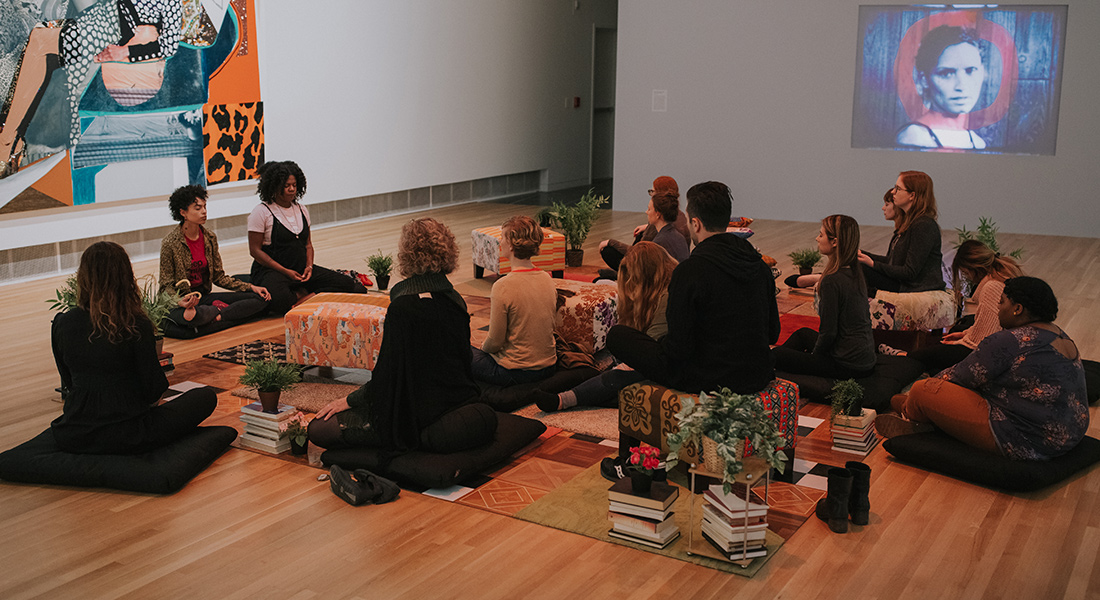 A group of people meditate in a gallery.