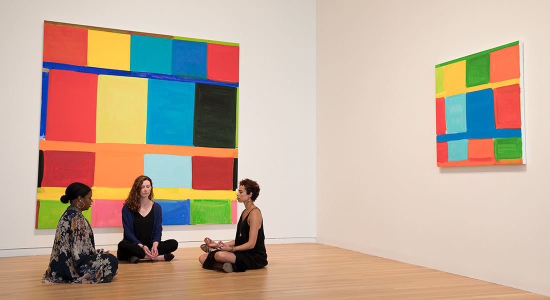 Three people meditate in front of two artworks.