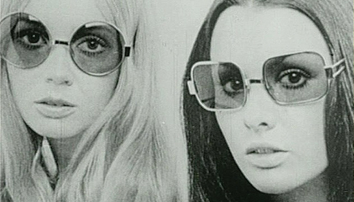 Photo image of two young white women with long straight hair, wearing sunglasses, from Julia Reichert & Jim Klein's 1970 documentary film Growing Up Female
