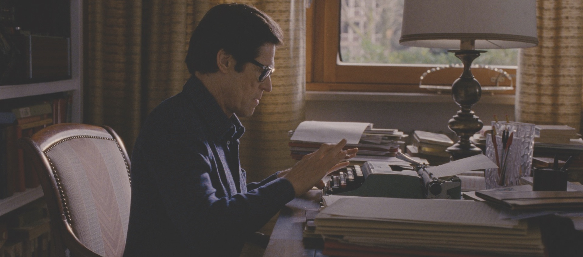 Willem Dafoe as filmmaker Pier Paolo Pasolini sits at a desk and types in a still from Abel Ferrar's biopic Pasolini, courtesy of Kino Lorber Films