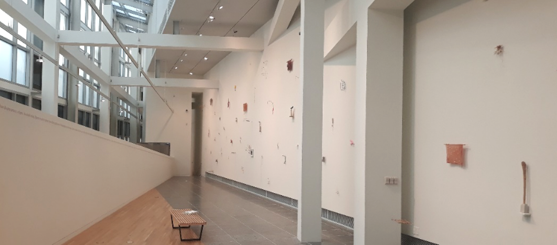 An image shot from above of Gallery B in the Wexner Center for the Arts at The Ohio State University. The image includes the white grid work near the ceiling of the center's galleries and an installation of precarios by artist Cecilia Vicuña.