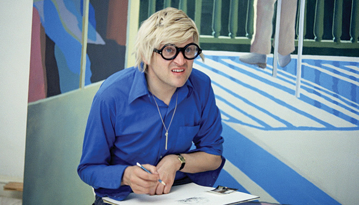 An image of British artist David Hockney sitting in front of one of his paintings in a scene from Jack Hazan's 1973 film A Bigger Splash