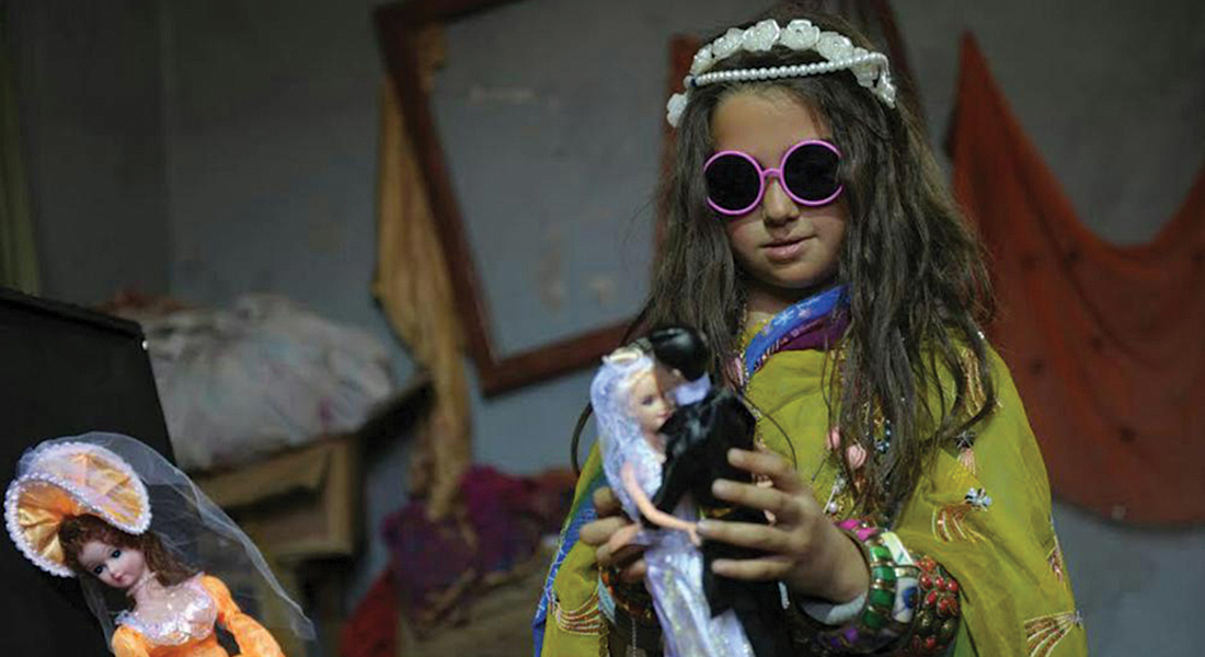 Little girl in sunglasses playing with dolls