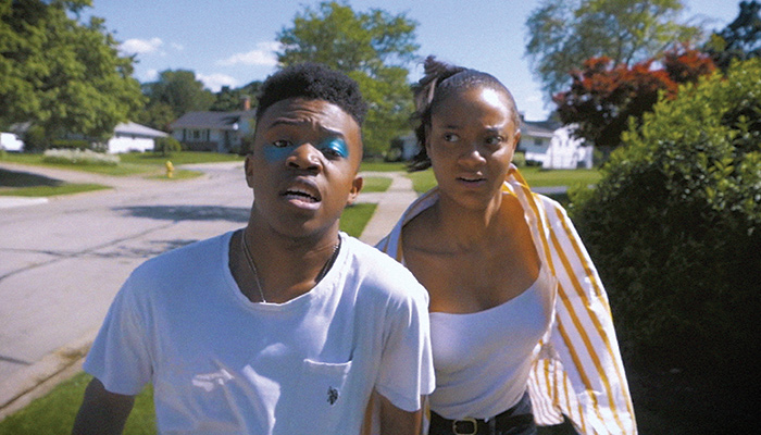 Head & shoulders images of a young black man and woman running down a suburban street in a scene from the short film COVE (Illegal Alien) by Ryan Wise
