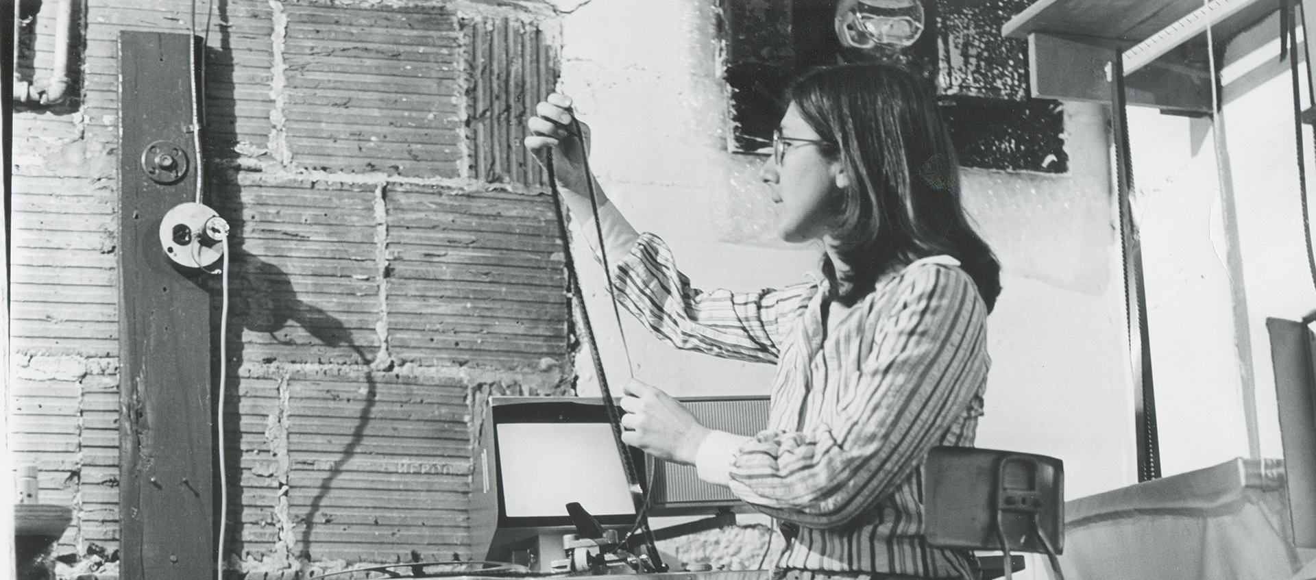 A black-and-white archive image of Julia Reichert seated and looking at a reel of film in her studio
