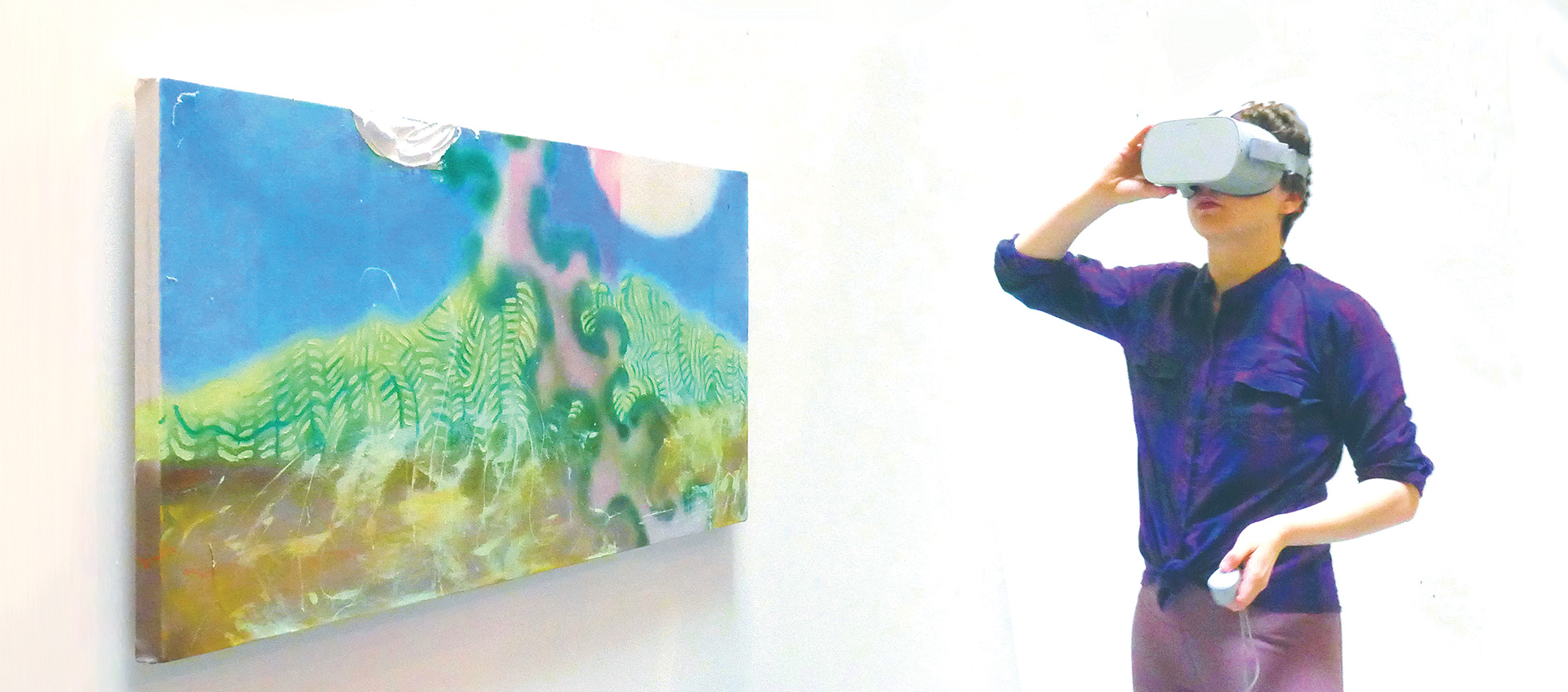 Person wearing virtual reality goggles next to colorful painting