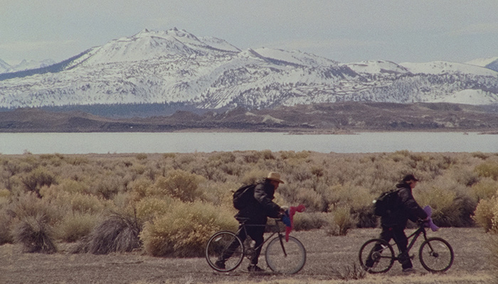 two young adults riding bicycles with snow-covered mountains in the background