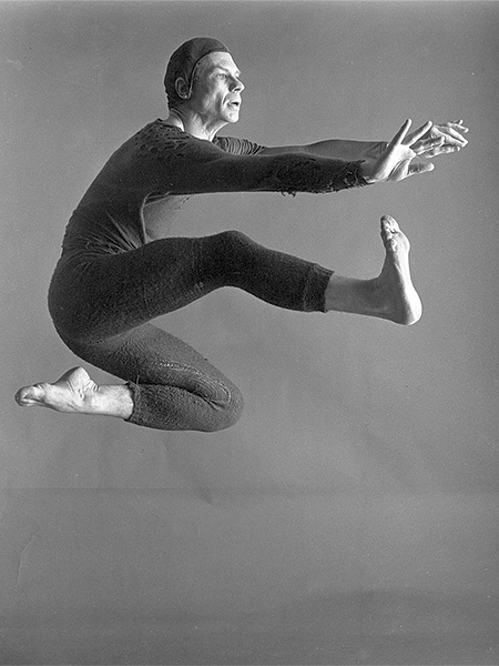 Black and white portrait of dancer-choreographer Merce Cunningham, caught mid-jump.