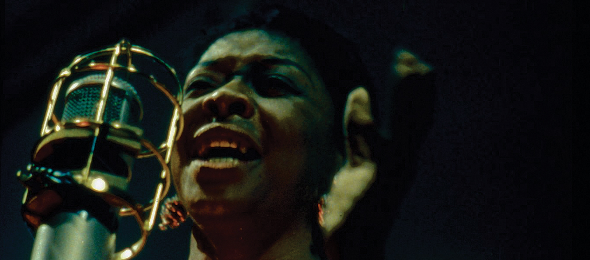 Dinah Washington, seen from neck up, sings into a large bullet microphone in a scene from the documentary Jazz on a Summer's Day