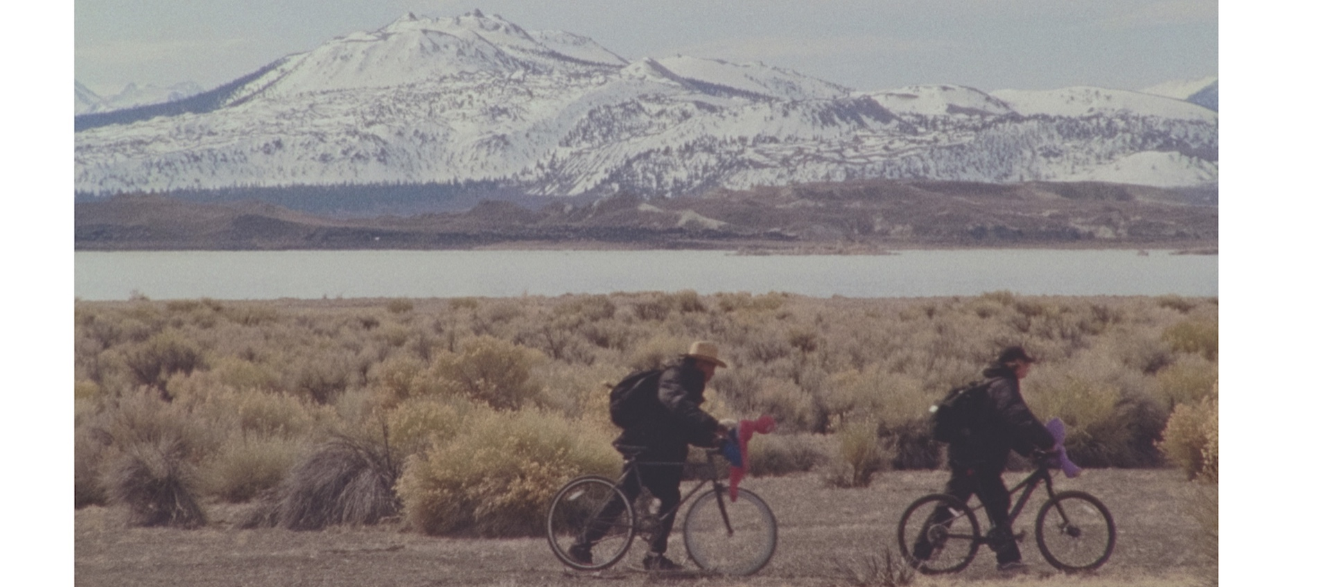 Two teenage boys ride bikes against a gray mountain-filled background in an image from artist Stanya Kahn's short film No Go Backs