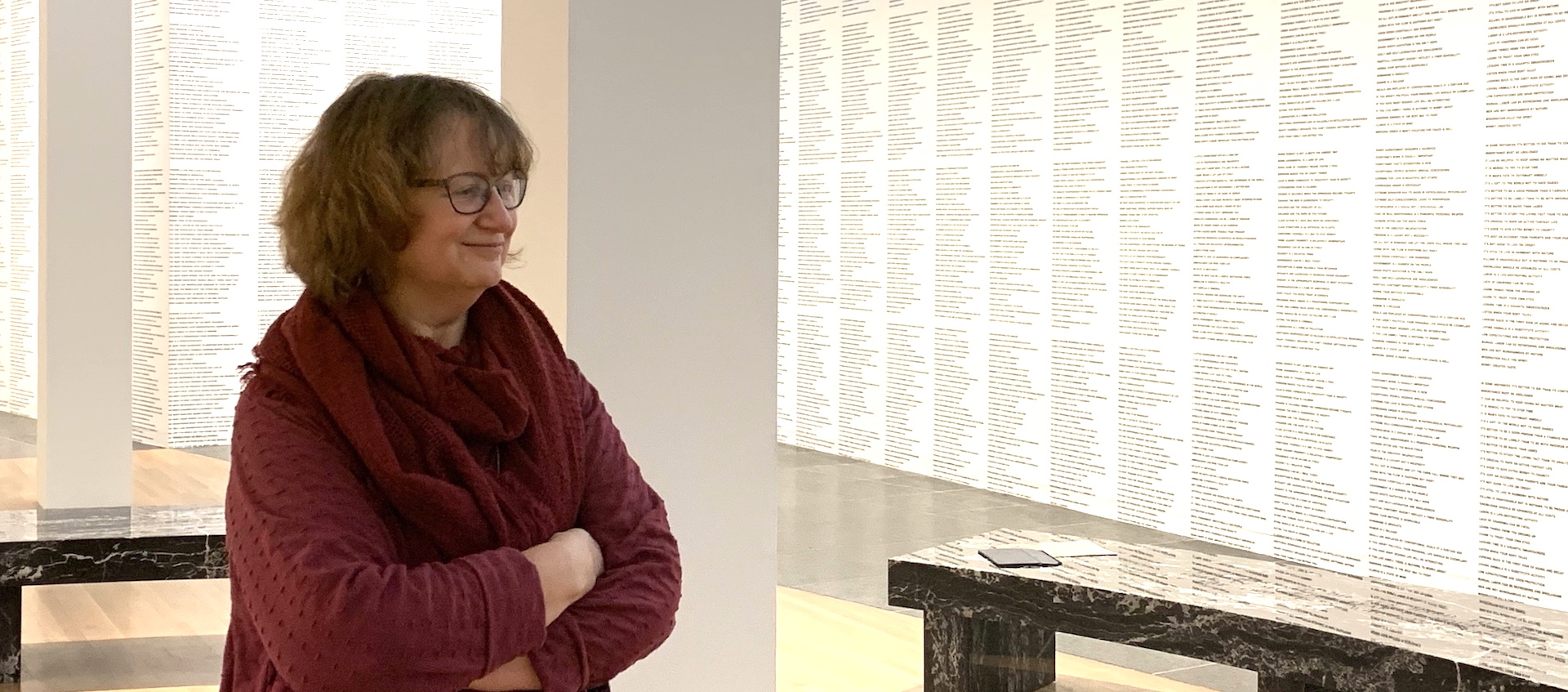 Ohio State professor of English Elizabeth Weiser stands with her arms folded in a gallery covered floor to ceiling with text by artist Jenny Holzer during a gallery talk at the Wexner Center for the Arts