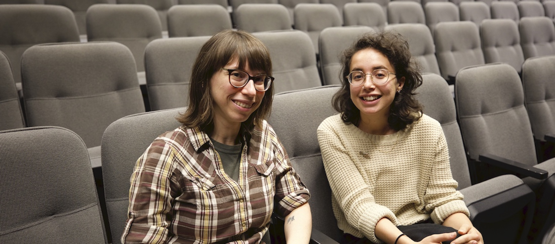Wexner Center for the Arts projectionist Rachael Barbash and Film/Video program assistant Layla Muchnik-Benali sitting in an otherwise empty screening room