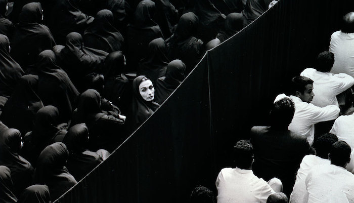 A black and white dual projection image of gender-segregated crowds from the Shirin Neshat video installation Fervor