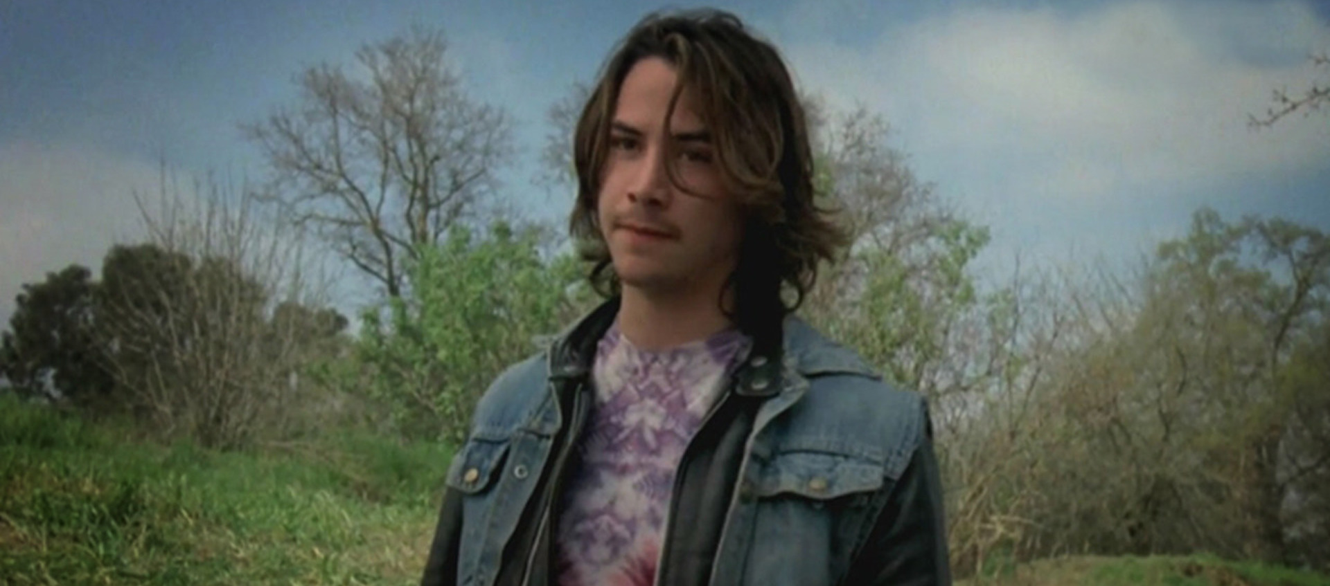 Color image of a young Keanu Reeves standing outdoors in front of grass and trees during the production of Tim Hunter's 1984 film River's Edge