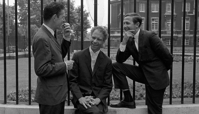 A black and white image of choreographer Merce Cunningham sitting against a tall iron fence, looking at the camera. He sits between composer John Cage and artist Robert Rauschenberg, who are both standing and facing each other