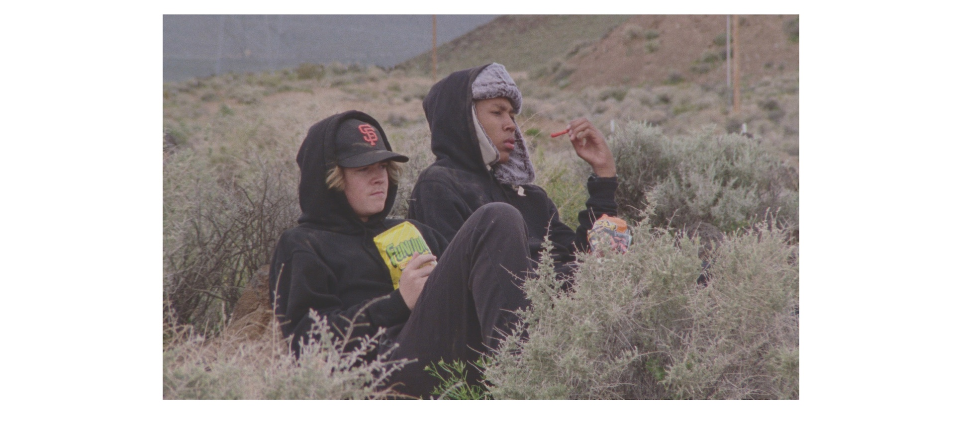 Two teenage boys in parkas sit in the brush near the Sierra Nevada mountain range in a scene from Stanya Kahn's short film No Go Backs
