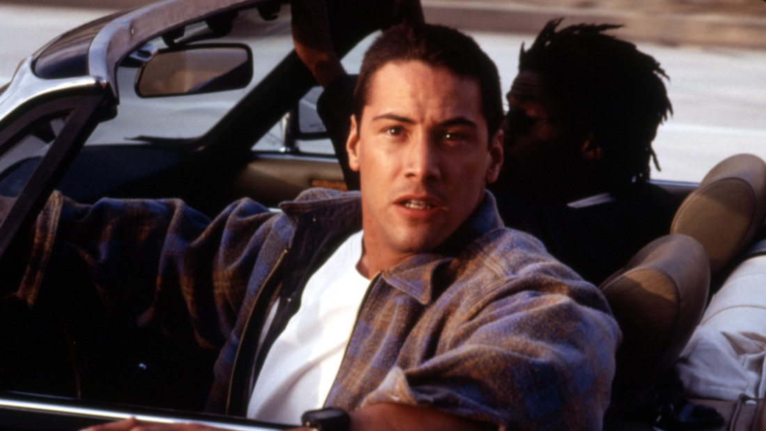 A color image of Keanu Reeves facing the camera while in the driver's seat of a car in a scene from Jan de Bont's 1994 film Speed