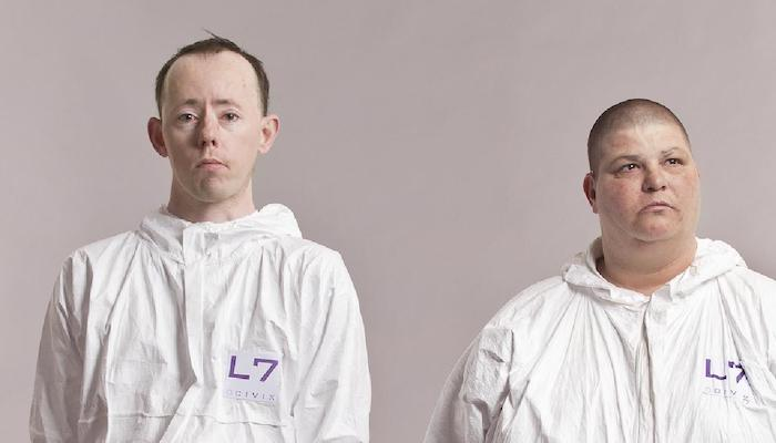 Back to Back Theatre company members Simon Laherty and Sonia Teuben in white hazmat outfits, seen standing shoulders up against a solid beige background