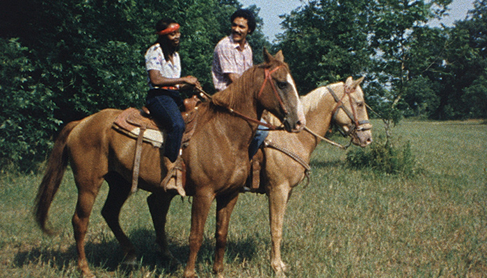 The young couple at the center of Cane River talk while riding horses together in a meadow.