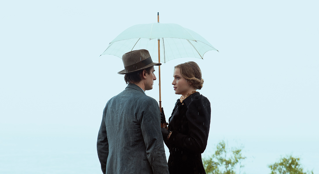 Martin and Elena face one another as they share a small umbrella in the rain.