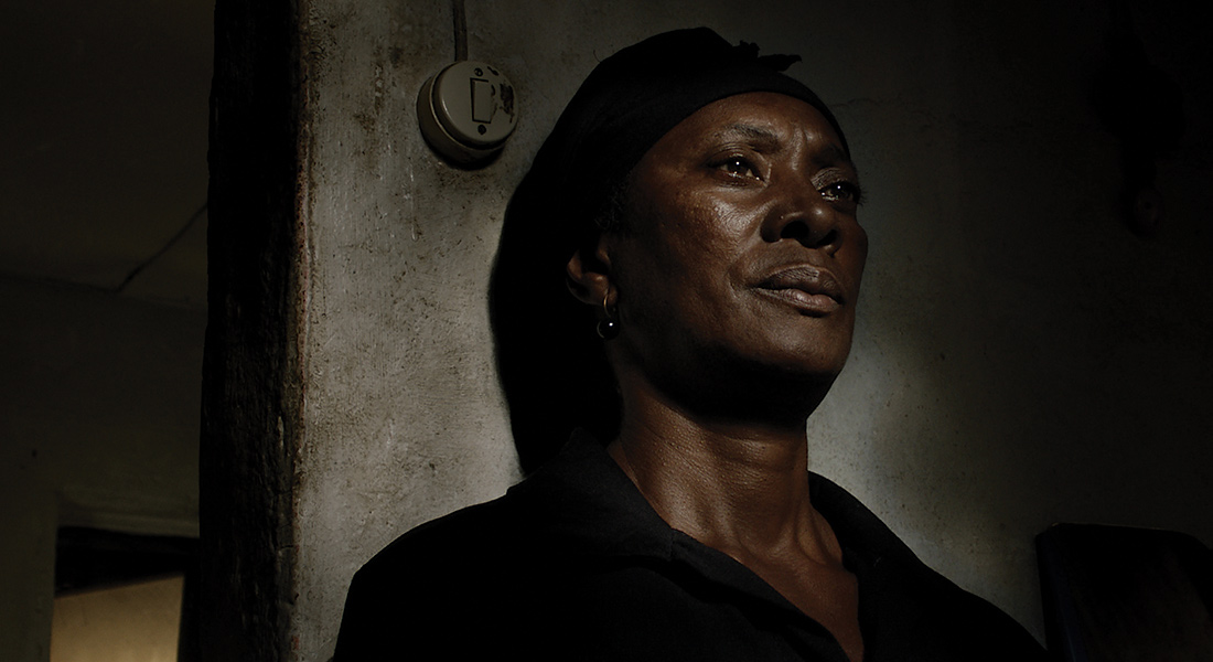 Tears fill Vitalina's eyes as she leans against a bare, rough interior wall.