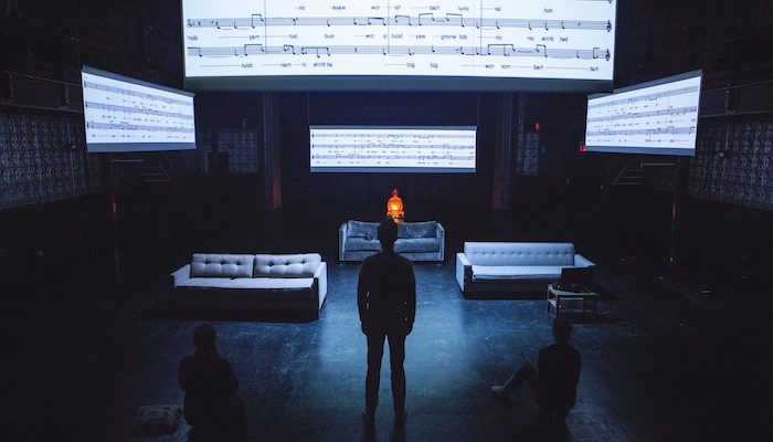 A man stands with his back to the camera on a darkened stage with individuals sitting on either side of him as he looks up at screens showing the notes in a music composition in a scene from Annie Dorsen's performance work Yesterday Tomorrow