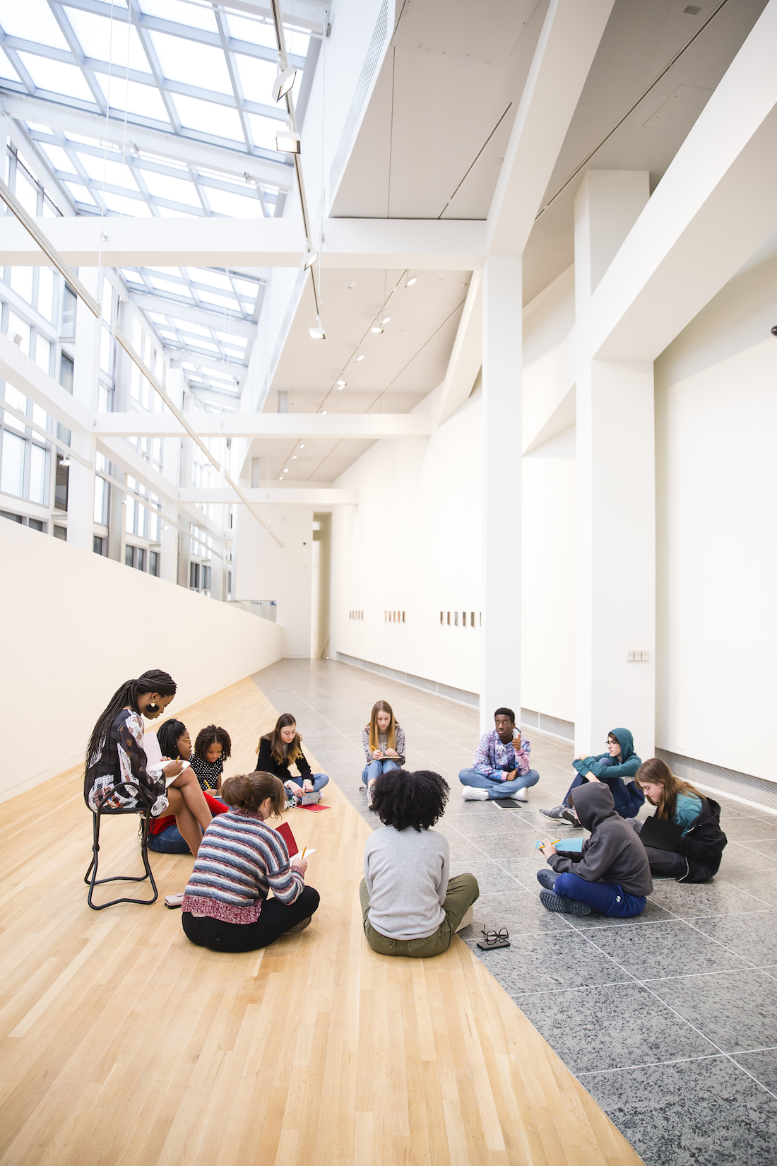 A group of 11 high school students and educators sit in a circle in a gallery at the Wexner Center for the Arts