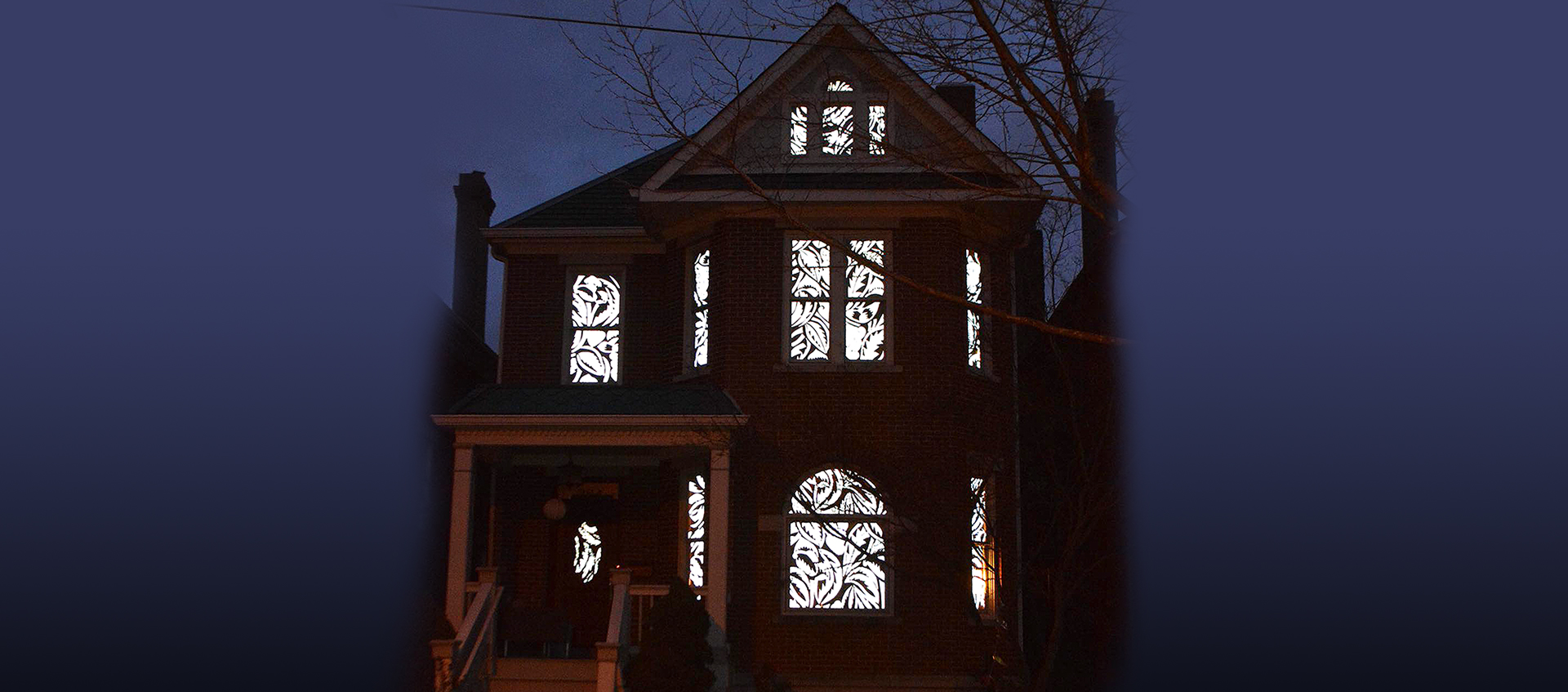 Antique patterns activated by light in the windows of a three-story Victorian home