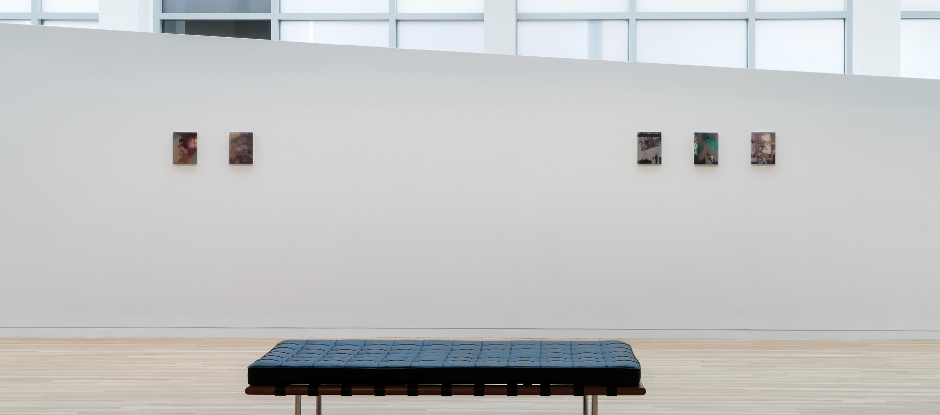 a black bench in front of a white wall with art pieces on it