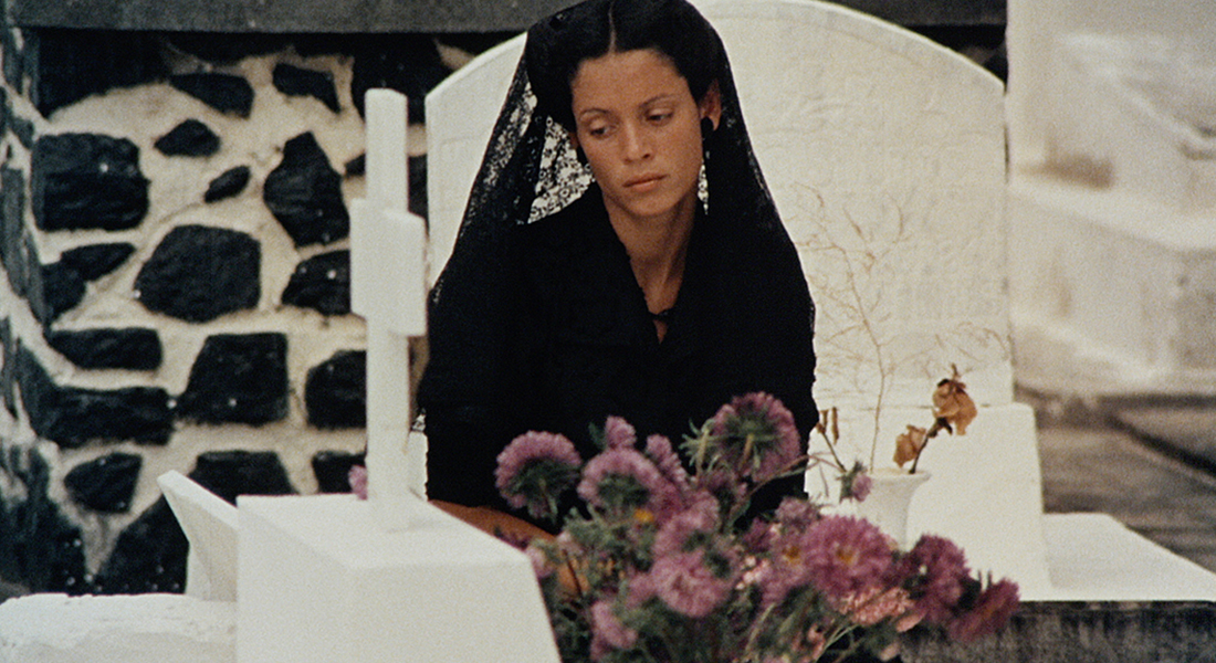 Dona Flor dressed in mourning attire in front of a grave.