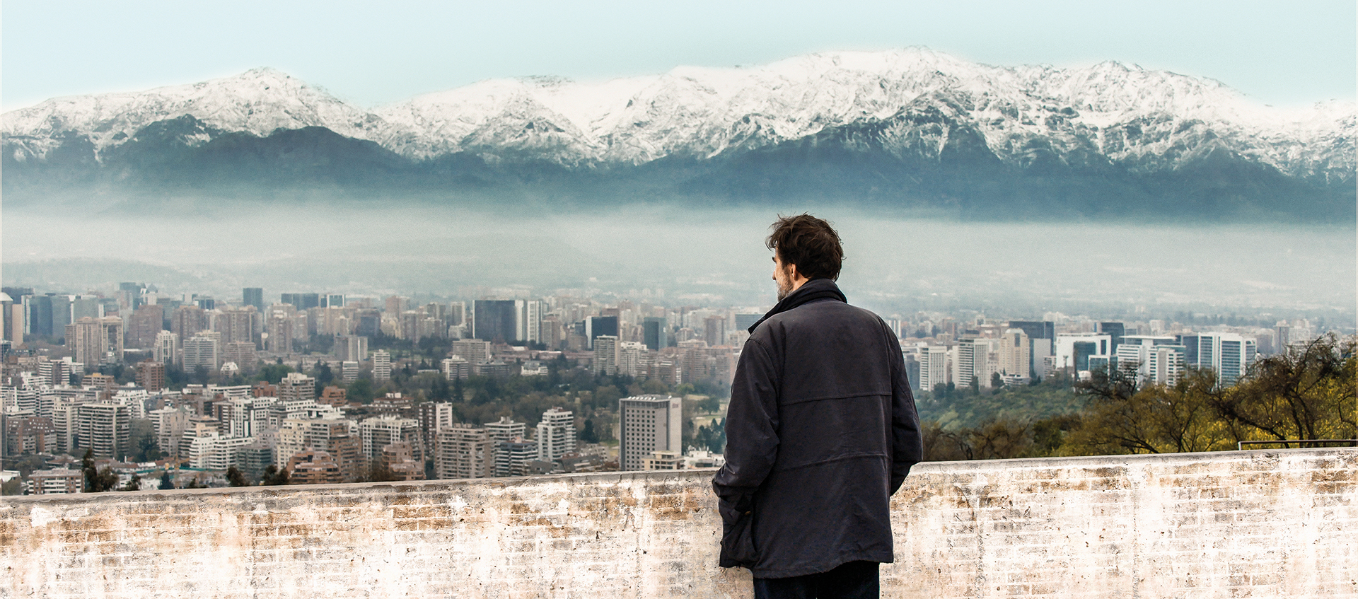 a man in a black coat overlooking a city with mountain in the background