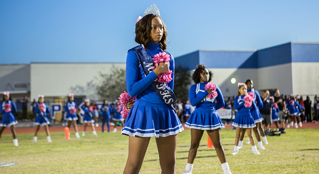 cheerleaders in a field wear blue uniforms and pink pompoms