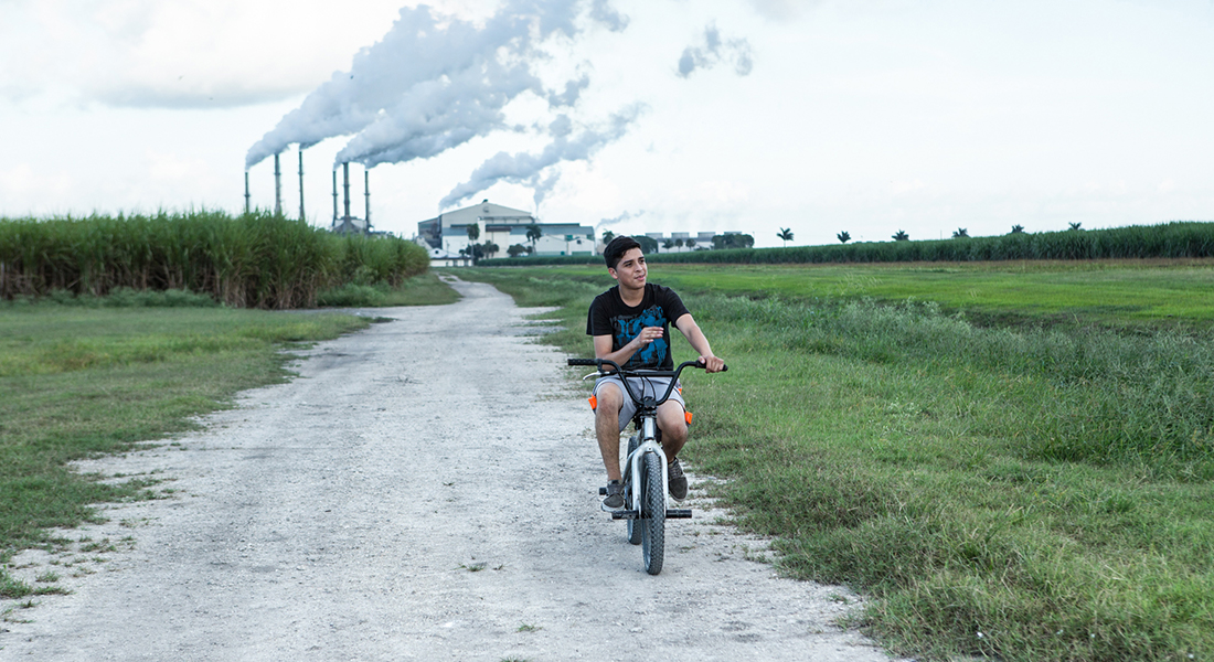 a boy riding a bike on a dirt road with industrial smoke stacks in the background