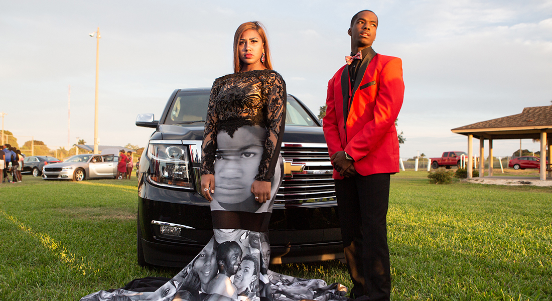 a boy in red and black suit and girl in black and print dress posing in front of an SUV