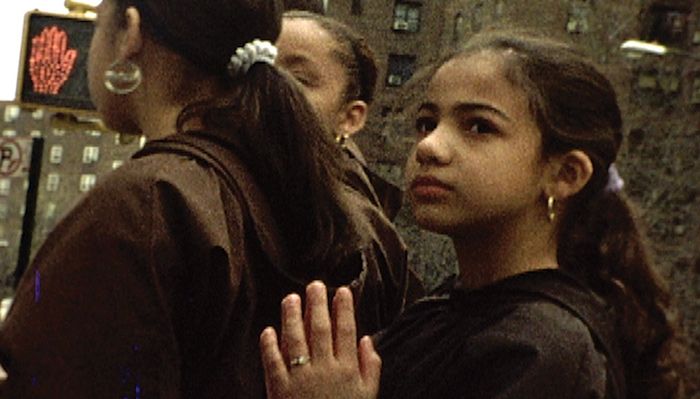A young girl stands on a street corner behind a woman and looks to the left in a scene from Jeanne Liotta's video work Crosswalk